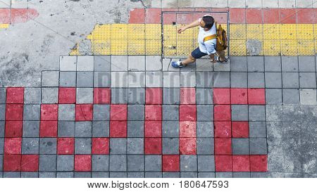 Aerial view and top view with blur man is walking in Business area with pedestrian and red and yellow block walkway
