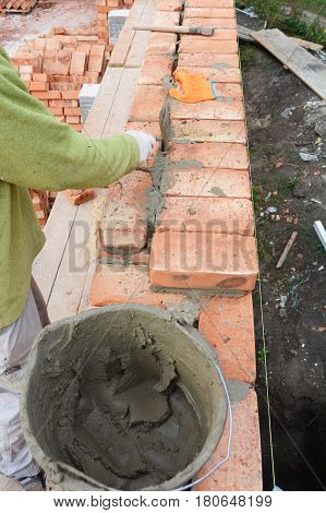 Bricklaying Brickwork.Bricklayer worker installing red blocks and caulking brick masonry joints exterior brick house wall with trowel putty knife outdoor.