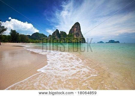 Famous limestone cliffs of Krabi bay overlooking wide sandy beach off west coast of Thailand