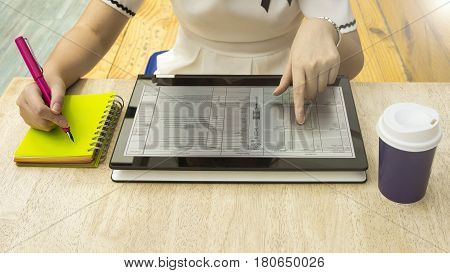 Woman are pressing and reading a tablet touch on screen text ebook over a table at cafe with the notebook and pen in the left hand side and coffee cup on the right side on the wood table.