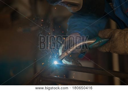 a worker with protective mask welding metal
