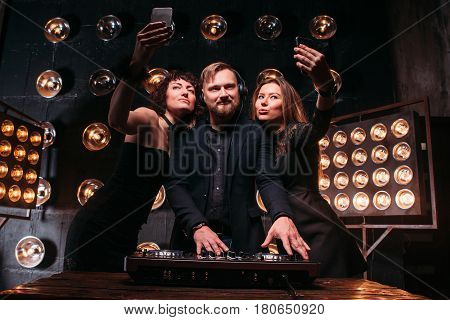 Two beautiful sexy and fashionable girls making selfie on phone with handsome bearded disk jockey at the DJ mixer. Party, relax and fun, clubbing, nightlife.