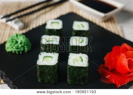 Appetizing set of sushi maki with cucumber served on black slate, close up. Japanese food, traditional asian cuisine. Vegetarian rolls.