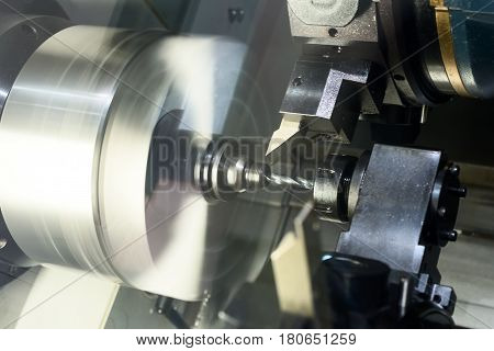 The CNC lathe processes the metal part. Abstract industrial background.