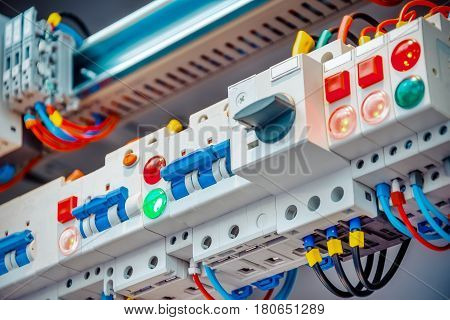 A fragment of circuit breakers block DIN rail Industrial abstract background.