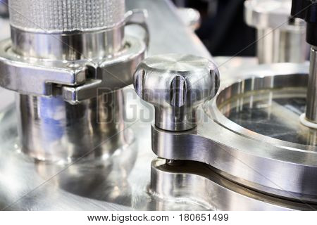 Pharmaceutical equipment, a fragment of the compression lid. Stainless steel. Abstract industrial background.