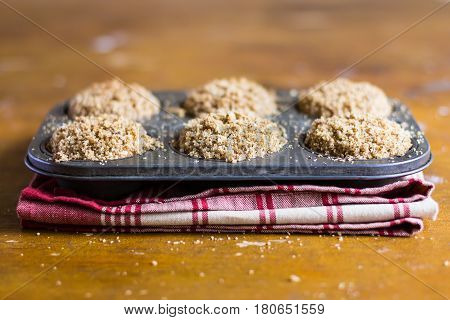 Homemade whole wheat muffins or cakes with cardamom, cinnamon, nutmeg, walnuts and brown sugar in a baking dish on a wooden table, selective focus