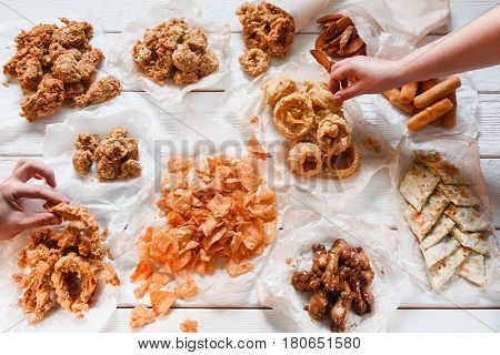 Appetizing fresh beer snack assortment on white wooden table, flat lay. Junk food, unhealthy eating, calories. Unrecognizable person take pieces, dining, buffet
