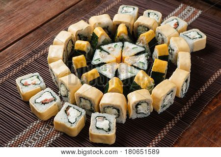 Appetizing tasty great sushi set served on straw mat, top view. Food art, colorful mosaic, restaurant menu photo. Japanese traditional seafood.