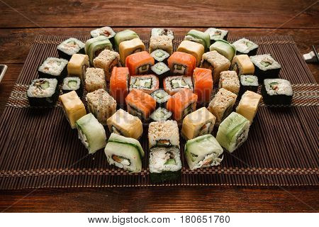 Tasty great colorful set of fresh japanese sushi maki rolls served on brown straw mat, close up. Food art, traditional seafood, luxury restaurant menu photo.