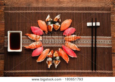 Delicious appetizing set of colorful nigiri sushi served as circle on brown straw mat, flat lay. Japanese traditional seafood.