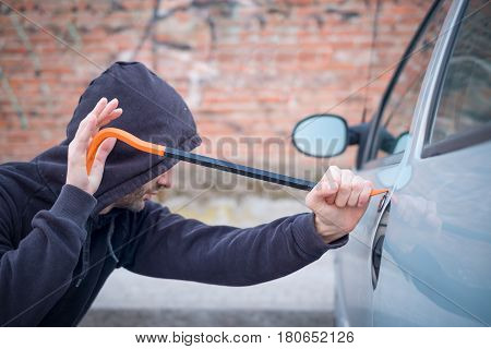 Thief Trying To Pick The Lock Of Parked Car