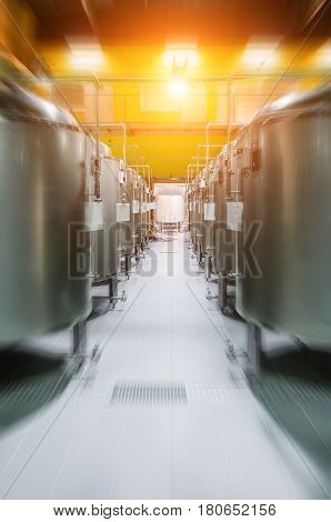Modern Beer Factory. Rows of steel tanks for the storage and fermentation of beer. Motion blur effect, sunlight