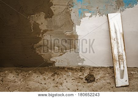 plastering tools lying near the plastered wall