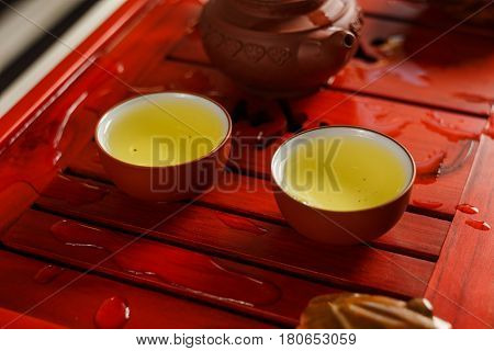 Two Bowls With Fresh Oolong Tea On Tea Desk.