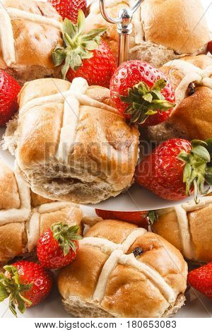 british hot cross buns and sweet strawberries on a cake stand