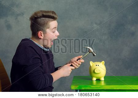 Teenager Open Piggybank With Hammer