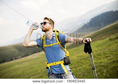 Young Hiker Stopped And Drink Water From A Bottle