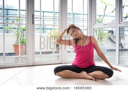 Young fitness woman stretching side of her neck