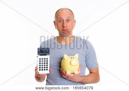 Man In Gray Shirt With Pocket Calculator And Piggybank