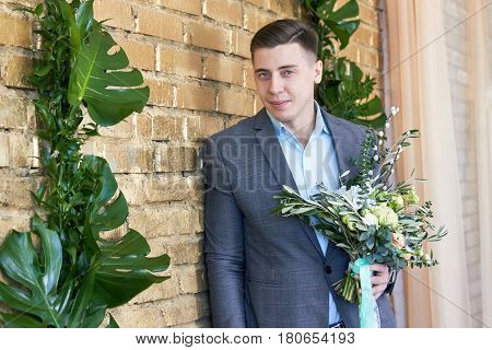 Groom preparing for the wedding. Future husband is waiting for his future wife.A man in a wedding suit poses for the photographer before the wedding. Portrait of a happy man