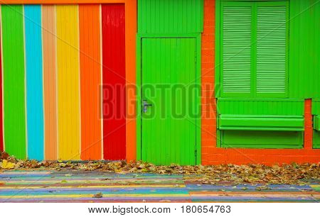 Colorful house. Bright colorful wall facade with green door and wooden window