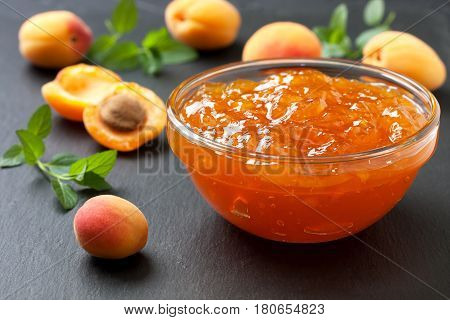 Apricot jam in a glass bowl fresh apricots on black slate background