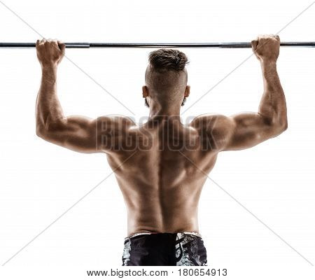 Exercise for the back. Photo of muscular fitness model doing pull ups on white background. Back view.