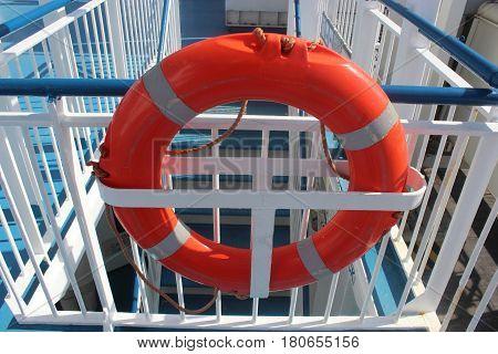 orange life buoy on the railing of a ship
