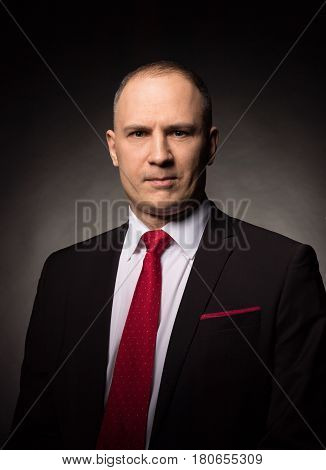 Confident businessman in black wearing suit and red tie