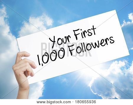 Paper With Text Your First 1,000 Followers  . Man Hand Holding Sign On White Paper. Isolated On Sky