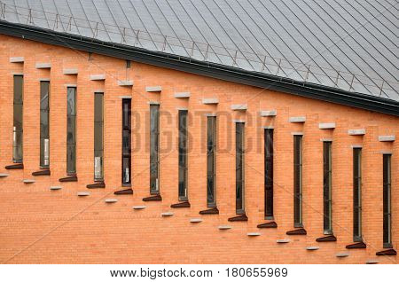 Architectural composition. Red brick wall with vertical glass inserts.