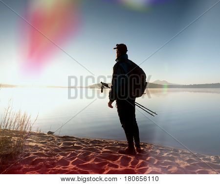 Tall Hiker In Dark Sportswear With Poles And Sporty Backpack Walk On Beach. Tourist Enjoy Sunrise