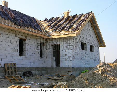 Roofing House Exterior. A roof under construction site with stacks of roof tiles ready to fasten outdoor.