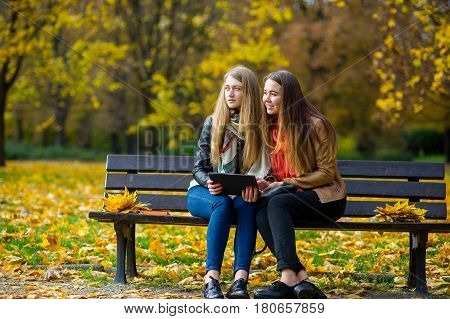 Two cute female student girls are sitting on a bench in an autumn park. In the hands of one of the girlfriends is a tablet. Girls somewhere with interest look. Ground is covered with fallen leaves.