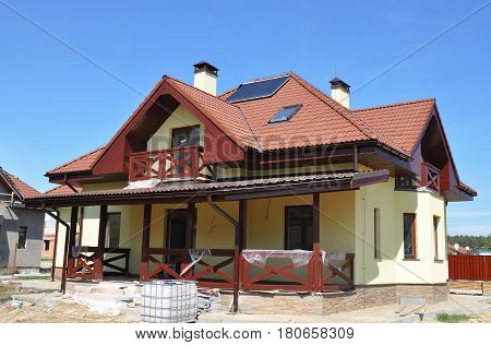Energy Efficiency New Passive House Building Concept Outdoor. Closeup on Solar Water Heater Dormers Gutter Solar Panels Skylights Lightning Protection Installed on Red Tiled House Roof Exterior.