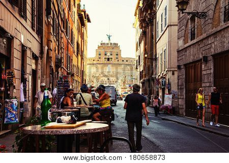 ROME, ITALY - JULY 12, 2015: Street cafe with tourists, city life in the center of Rome, Italy. Castle of the Holy Angel at the background, famous landmark in Rome