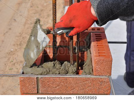 Bricklayer worker installing red blocks and caulking brick masonry joints exterior wall with trowel putty knife outdoor. Bricklaying Masonry.