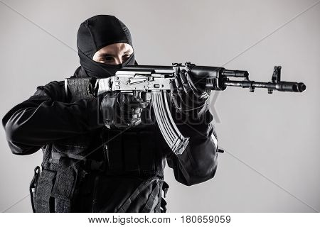 Special Forces Soldier Man Hold Machine Gun On A Grey Background