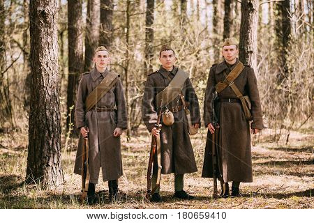 Pribor, Belarus - April 23, 2016: Three Re-enactors Dressed As Soviet Russian Red Army Infantry Soldiers Of World War II Posing With Rifles Weapons In Autumn Spring Forest