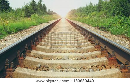 Early morning sun light and train rail road track sleepers. Rural landscape during summer sunrise background. Transportation, perspective industrial concept
