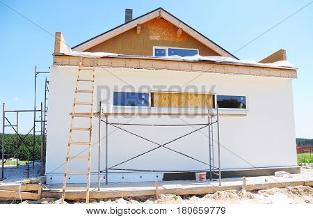 Attic Insulation. Construction or repair of the rural house with insulation eaves windows garage chimney roofing fixing facade plastering. Unfinished house. Insulation House with mineral wool.