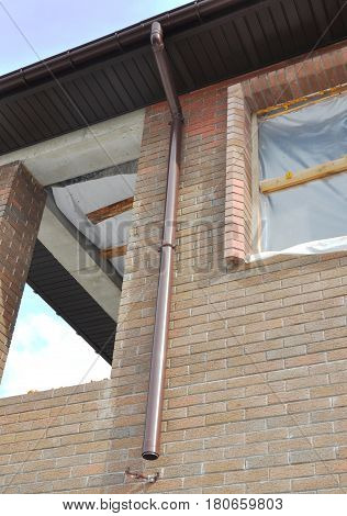 Guttering. New Rain Gutter Drain Pipe Downspout Installation on the Unfinished House Facade Brick Wall. Guttering with Install drainage system