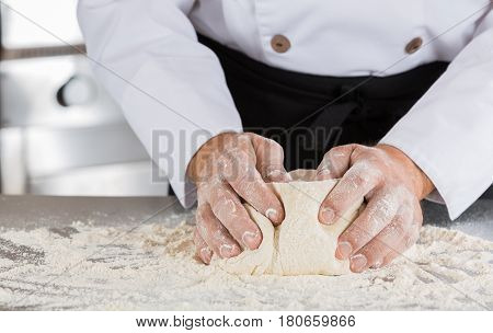Baker kneading dough with flour and water