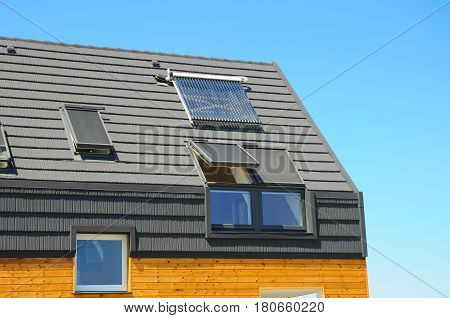 Closeup of Solar Water Panel Heating Dormers Solar Panels Skylights Ventilation and Air Conditioning Systems Installed on House Roof. Energy Efficiency New Passive House Building Concept. Attic skylight.