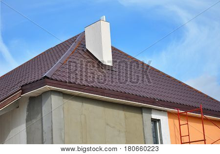 Construction or repair of the rural house with eaves windows chimney roofing fixing facade insulation plastering and painting walls. Painting House Facade Wall. Metal Tiled Roofing. Roof Repair.