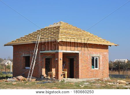 New Roof Membrane Coverings Wooden Construction Home Framing with Roof Rafters and Metal Ladder Outdoor against a Blue Sky. Roofing Construction Exterior.