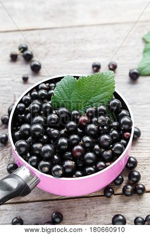 crop currant. currants in a pink pot on a wooden background. in the background is a currant and leaves.