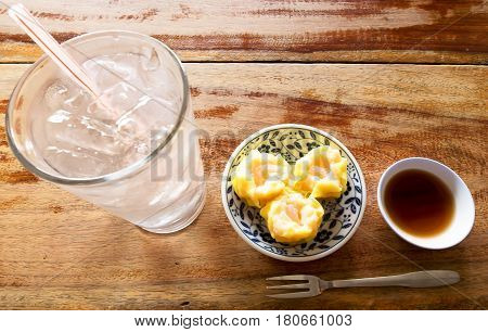Dim Sum with Soy souce and Glass of water on wood table