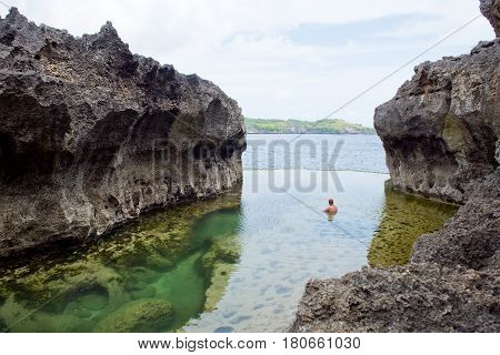 A man rests in a natural pool with water on the background of the ocean. Angel's Billabong Nusa Penida Indonesia.